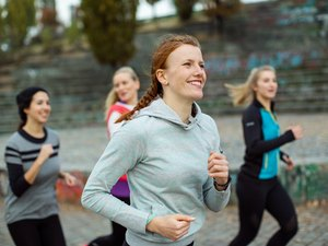 Fit woman with friends jogging in park