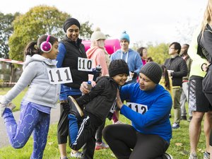 A family of runners preparing for a turkey trot, stretching in the park