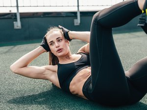 Woman doing crunches. Young female doing abdominal exercises outdoors.