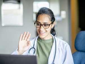 smiling doctor waving to patient on laptop during telemedicine appointment