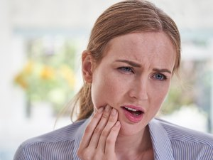 Woman in pain holding the right side of her jaw
