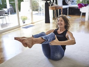 Happy mature woman exercising at home