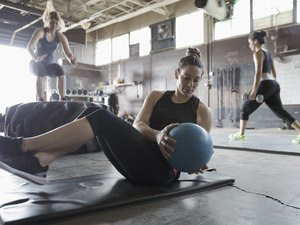 Focused, strong woman doing seated medicine ball twist in gritty gym