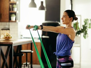 Smiling female athlete practicing with a resistance band at home.