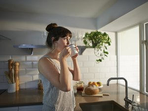 Woman drinking coffee in the morning in her kitchen