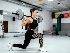 Woman doing weighted lunges with barbell on back.