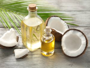 Bottles with fresh coconut oil palmitic acid on wooden table