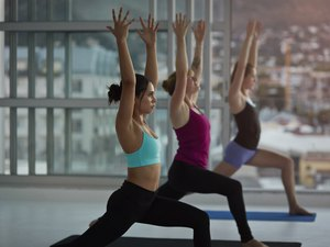 Women wearing yoga clothes streching arms at yoga session