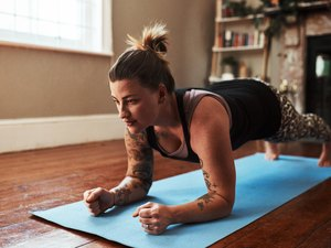 Woman doing a forearm plank during an at-home workout on a blue yoga mat