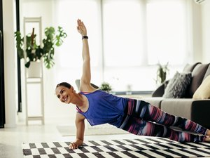 woman doing side plank for amrap ab workout at home