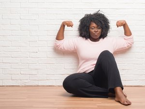 Young african american woman sitting on the floor at home showing arms muscles smiling proud. Fitness concept.
