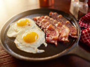 Fried bacon and eggs in an iron skillet