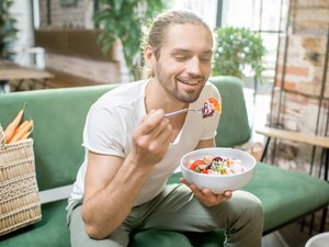 Vegetarian man eating salad indoors