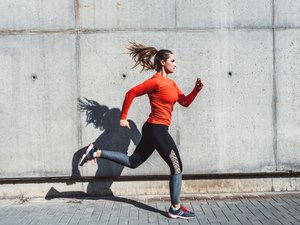 woman in red longsleeve and black leggings running outside