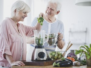 Happy older couple on a diabetes diet making healthy smoothies at home