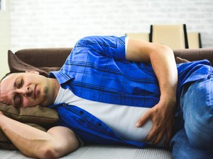 Man lying on sofa looking sick in the living room