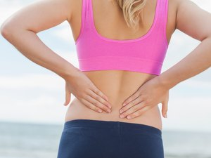 Mid section of toned woman from back pain on beach