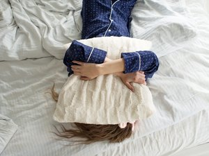 Too lazy to get out of bed, a woman covers her face with a pillow
