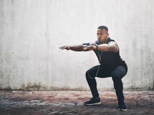 Man trying to do a squat against a concrete wall