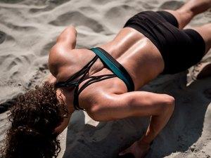 Women athlete doing workout on the beach