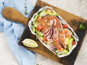 Raw salmon steak with vegetables in a foil boat
