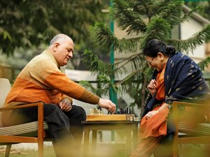 couple seated in garden playing chess