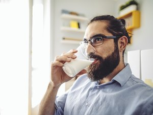Man drinking glass of milk at home