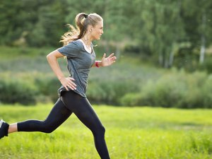 Woman listening to music and running in park