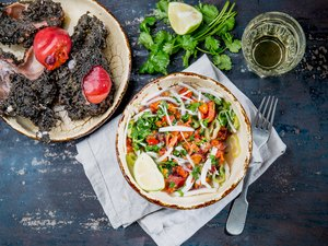 PIURE CEVICHE SEBICHE in plate and ingredients. Top view. Ceviche from chilean and peruvian seafood piure pyura chilensis, white wine, piure in rock, cilantro and lime