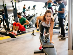 Young woman doing dumbbell exercises at gym