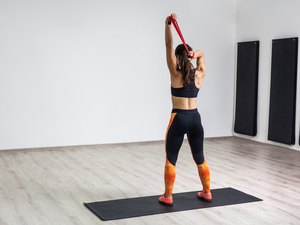 Portrait of athletic body fitness girl in black top and orange leggings performs exercises for the muscles of the back and hands with resistance band on white wall.