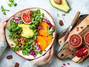 Top view of salad bowl filled with avocado, arugula, pomegranates, grapefruit and squash