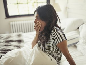 A young woman yawning as she sits up in bed in the morning