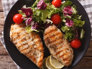 Close-up view of grilled chicken breast with mixed salad