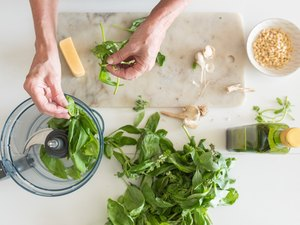 Woman's hands preparing basil for pesto from above