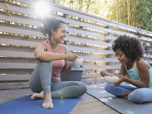 what to eat before a workout mother and daughter eating cereal on yoga mats on deck