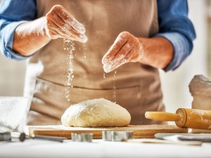 Hands preparing dough in kitchen for bread
