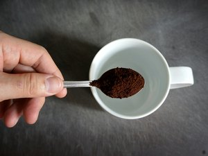 Hand Holding Spoon Of Coffee Powder Over Cup
