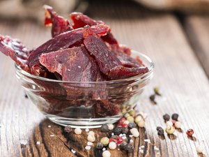 Biltong beef jerky on wooden background