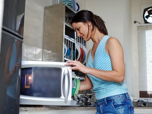 A woman using a microwave oven