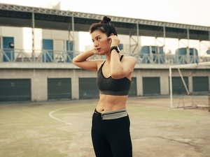 Portrait of a Runner: Fit Asian Woman With Wireless Earphones Ready to Run