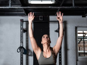 Young fit strong sweaty muscular girl with big muscles preparing for hard core abs or abdominal cross workout training on the pull up bar in the gym selective focus real people exercise