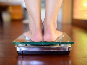 A view from the back of feet on a bathroom scale