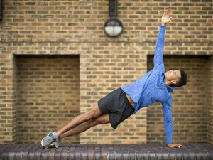 Man doing a side plank in front of brick wall, Wapping, London, UK