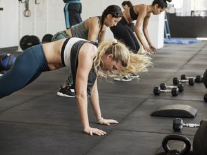 Athletes doing burpee exercise in crossfit gym