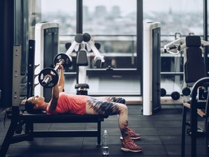 Young determined sportswoman exercising bench press in a gym.