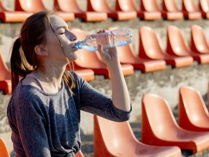 Young woman in sportswear relaxing after hard workout sit and drink water from special sport bottle after running on a stadium