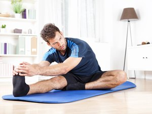 man doing a hamstring stretch sitting on blue yoga mat at home