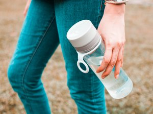 A young woman is holding a reusable water bottle container outdoors