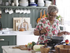 Active senior woman cooking in kitchen